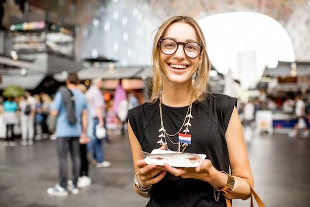Jonge vrouw die haring eet met uien traditionele nederlandse snack op de rotterdamse markt