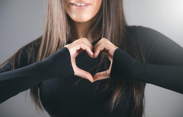 Jonge vrouw die hart op grijze achtergrond toont