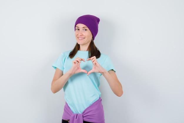 Jonge vrouw die hartgebaar toont in blauw t-shirt, paarse muts en er vrolijk uitziet, vooraanzicht.