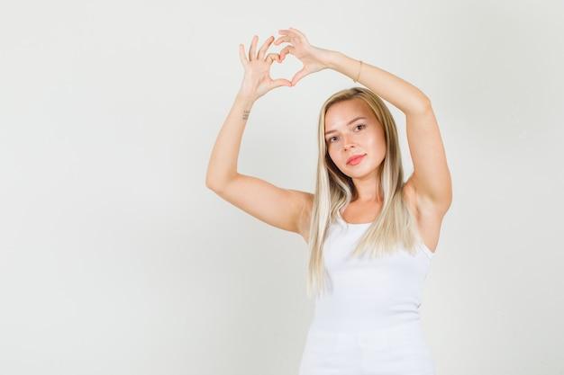 Jonge vrouw die hartvorm boven het hoofd in hemd maakt