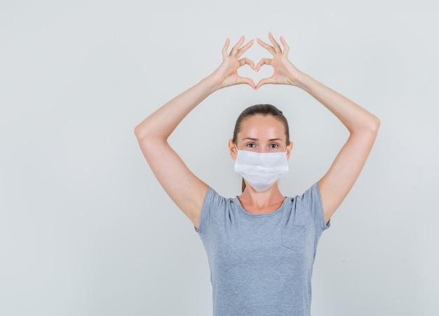 Jonge vrouw die hartvorm met vingers in t-shirt, masker maakt en vrolijk, vooraanzicht kijkt.