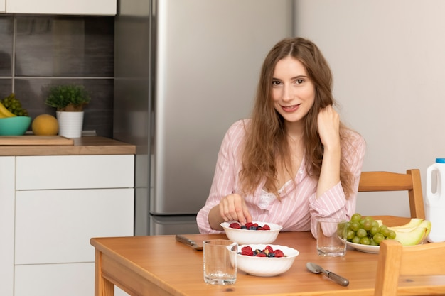 Jonge vrouw die havermout met fruit eet