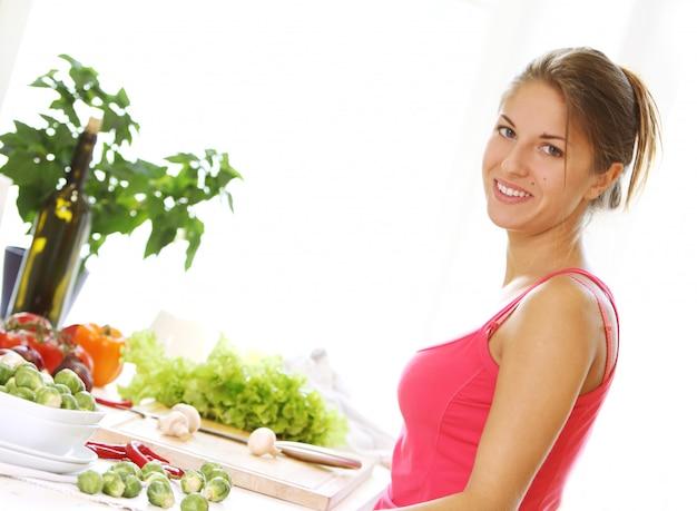 Jonge vrouw die healthly voedsel kookt