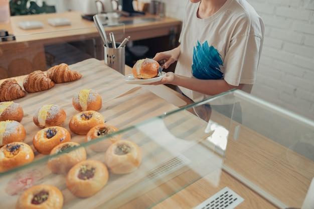 Jonge vrouw die heerlijk broodje op plaat plaatst