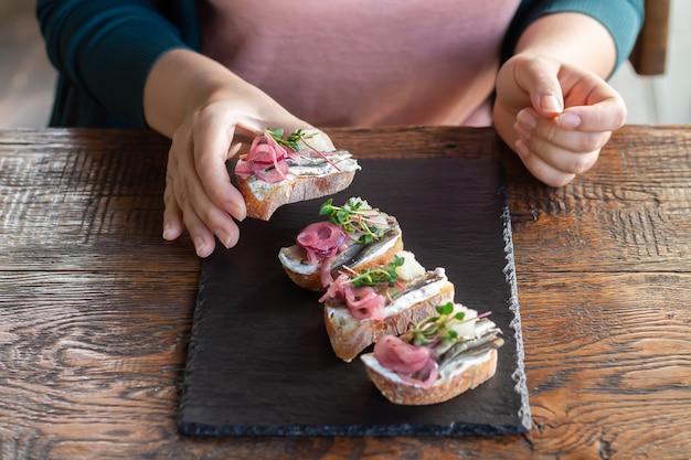 Jonge vrouw die heerlijke open sandwiches met gerookte vis, roomkaas, kaviaar en microgreen eet