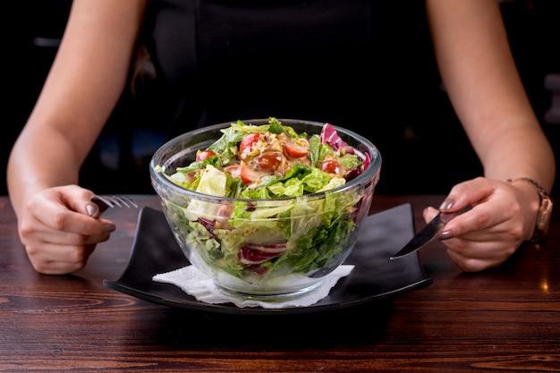 Jonge vrouw die heerlijke tonijnsalade, voedzaam en gezond voedsel eet - caloriearm dieet