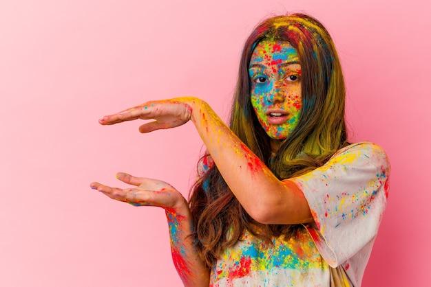 Jonge vrouw die heilig festival viert dat op witte muur wordt geïsoleerd die geschokt en verbaasd een exemplaarruimte tussen handen houdt