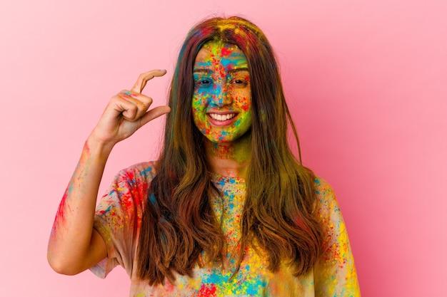 Jonge vrouw die heilig festival viert dat op witte muur wordt geïsoleerd die iets kleins met wijsvingers houdt, glimlachend en zelfverzekerd