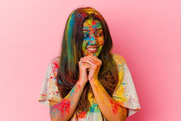 Jonge vrouw die heilig festival viert dat op witte muur wordt geïsoleerd, houdt de handen onder de kin, kijkt gelukkig opzij