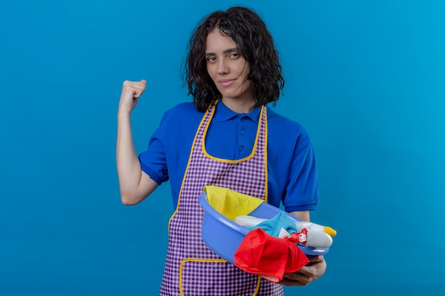 Jonge vrouw die het bassin van de schortholding met schoonmakende hulpmiddelen draagt die vuist opheft die bicepsen toont die zeker glimlachen glimlachen, klaar om over geïsoleerde blauwe muur schoon te maken