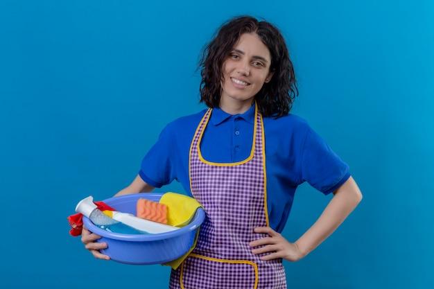 Jonge vrouw die het bassin van de schortholding met schoonmakende hulpmiddelen dragen die het zekere glimlachen vrolijk over blauwe muur kijken