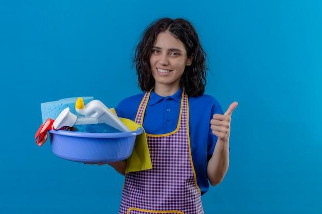 Jonge vrouw die het bassin van de schortholding met schoonmakende hulpmiddelen dragen die vrolijke tonende duimen over blauwe muur glimlachen