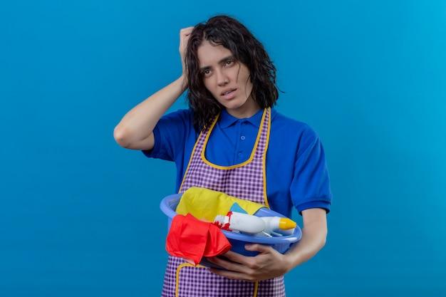 Jonge vrouw die het bassin van de schortholding met schoonmakende hulpmiddelen dragen wat betreft hoofd die overwerkt en vermoeid over blauwe muur kijken