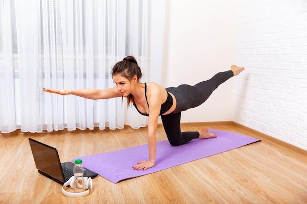 Jonge vrouw die het beoefenen van yoga bereikt door middel van yoga