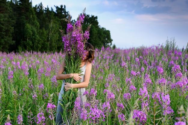 Jonge vrouw die het boeket van roze bloemen houdt.