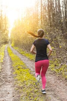 Jonge vrouw die het bos doorneemt