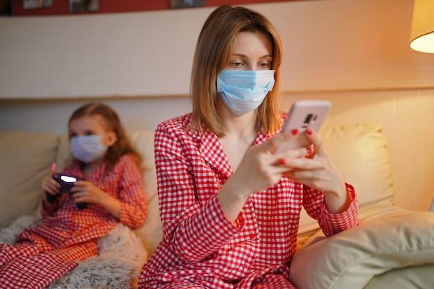 Jonge vrouw die het chirurgische verblijf dragen die van het gezichtsmasker thuis nieuws op smartphone kijken