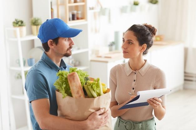 Jonge vrouw die het contract voor levering ondertekent terwijl de leveringsman die de producten houdt