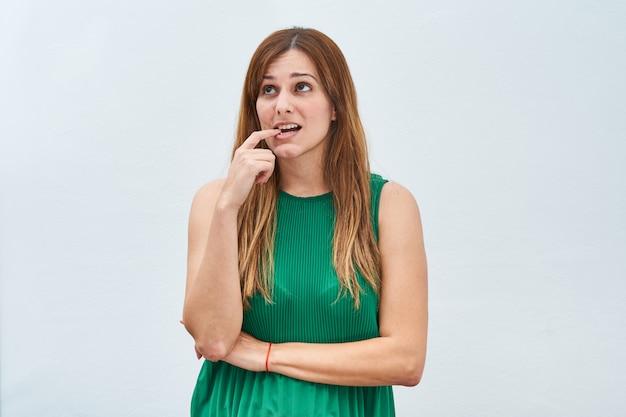 Jonge vrouw die het gebaar van het denken op een witte muur maakt.