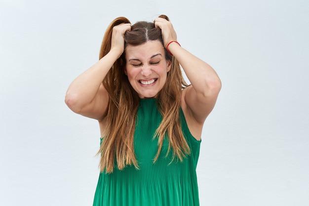 Jonge vrouw die het gebaar van het trekken van haar haar maakt en op een witte achtergrond benadrukt.