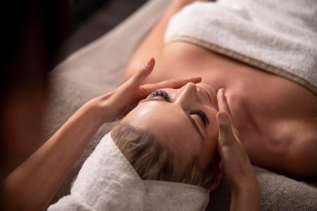 Jonge vrouw die het gezicht van haar cliënt masseert