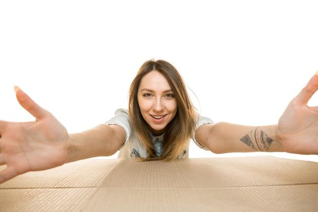 Jonge vrouw die het grootste postpakket opent dat op wit wordt geïsoleerd
