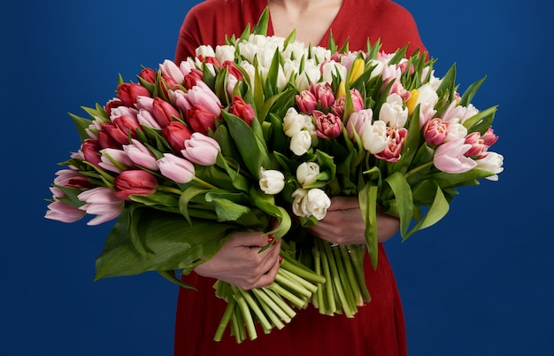 Jonge vrouw die het grote boeket van kleurrijke tulpen over blauw