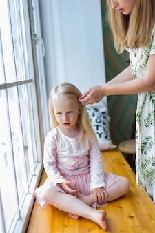 Jonge vrouw die het haar van het mooie meisje borstelen terwijl het zitten voor venster. vrouw die het haar van haar blonde dochter kamt