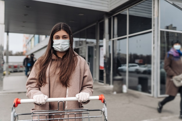 Jonge vrouw die het masker van het beschermingsgezicht draagt tegen coronavirus dat een boodschappenwagentje duwt.