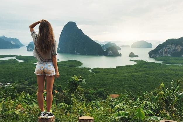 Jonge vrouw die het prachtige landschap in de baai van phang nga bekijkt
