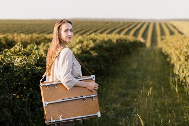 Jonge vrouw die het schilderen doos draagt