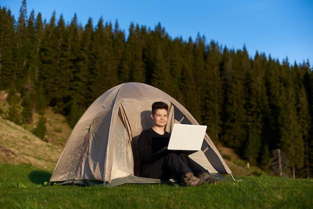 Jonge vrouw die het uitzicht bewondert terwijl het zitten in haar tent in de bergen en het werken aan laptop
