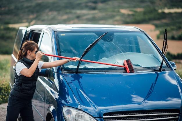 Jonge vrouw die het windscherm van blauwe bestelwagen schoonmaken