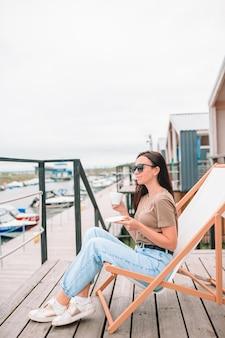 Jonge vrouw die hete koffie drinkt die van strandmening geniet.