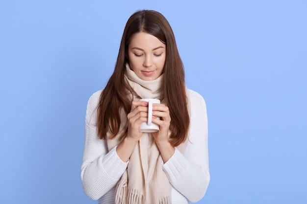 Jonge vrouw die hete thee drinkt, ziek is, die terwijl casual sweater draagt