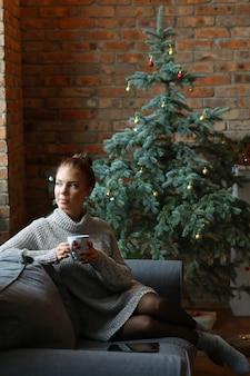 Jonge vrouw die hete thee op de bank drinkt