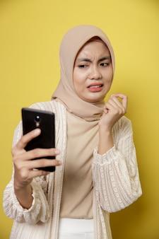 Jonge vrouw die hijab draagt met een uitdrukking die walgt terwijl ze naar haar telefoon kijkt die op gele achtergrond wordt geïsoleerd