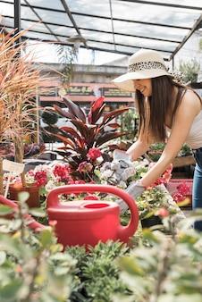 Jonge vrouw die hoed draagt die de bloemen op installatie met scharen snijdt