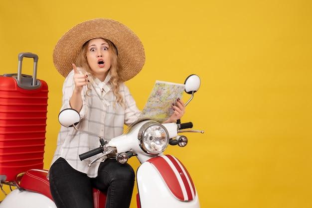 Jonge vrouw die hoed draagt en op motorfiets zit en kaart houdt die vooruit op geel wijst