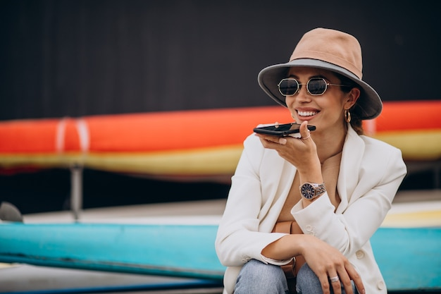 Jonge vrouw die hoed draagt en telefoon gebruikt