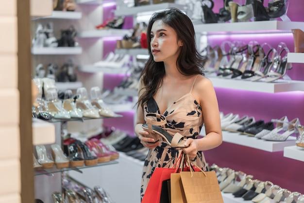 Jonge vrouw die hoge hielschoenen in winkel winkelt