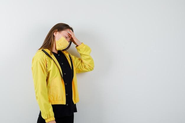 Jonge vrouw die hoofdpijn heeft en er uitgeput uitziet