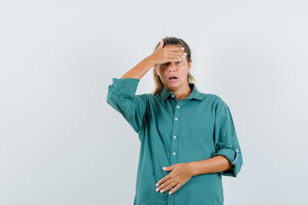 Jonge vrouw die hoofdpijn in groene blouse heeft en ernstig kijkt