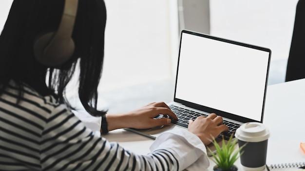 Jonge vrouw die hoofdtelefoons draagt en het geïsoleerde witte scherm van laptop computer met behulp van.