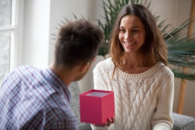 Jonge vrouw die huidig open giftdoos maakt aan echtgenoot maakt