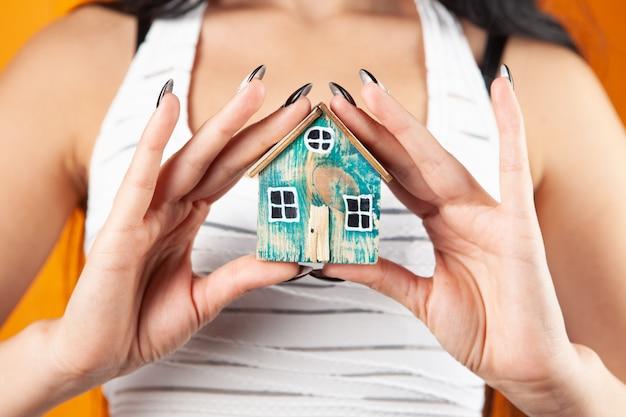 Jonge vrouw die huis in handen houdt