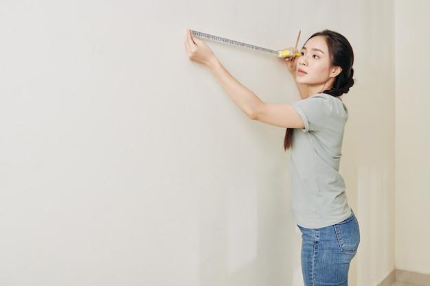 Jonge vrouw die huis renoveert