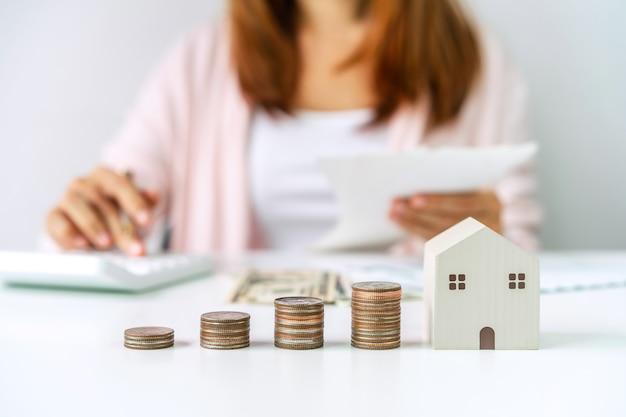 Jonge vrouw die huiskosten met stapel muntstukken berekent die geld voor het concept van vastgoedinvesteringen besparen