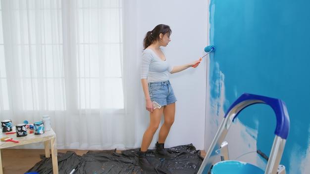 Jonge vrouw die huisreparaties doet en danst. muur schilderen met rolborstel gedrenkt in blauwe verf. appartement herinrichting en woningbouw tijdens renovatie en verbetering. reparatie en decoreren.