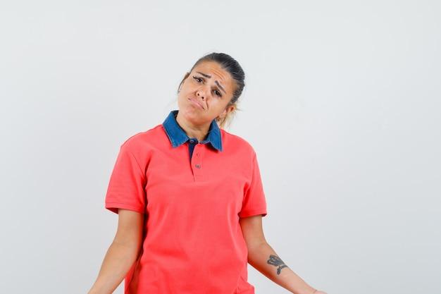 Jonge vrouw die hulpeloos gebaar en gebogen lippen in rood t-shirt toont en mooi kijkt. vooraanzicht.